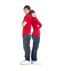 Full body playful young couple standing back to back