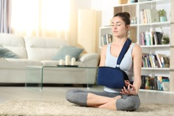 Full body portrait of a disabled woman with a broken arm in a sling practicing yoga exercise at home