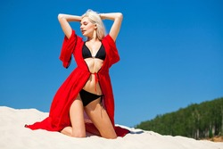 Full body portrait of a young beautiful blonde girl in black bikini and red tunic