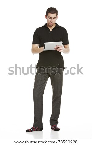 Full body portrait of a young handsome man working on a tablet computer