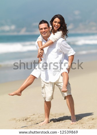 stock photo : Full body portrait of a young man giving piggyback to woman on beach. Couple in love enjoying a summer holiday.