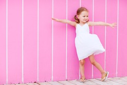 Full body portrait of adorable little girl outdoors against pink wall