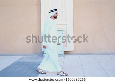 Full body portrait of Arab man walking on streets wearing Ghutra kandura. Emirati Arabic UAE National on dish dash. Side view of Arabian guy as he walks forward
