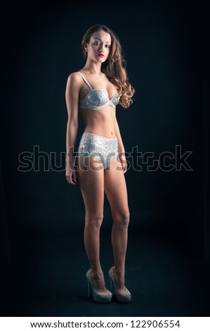 Full body portrait of beautiful sexy woman with shiny lingerie on black background.