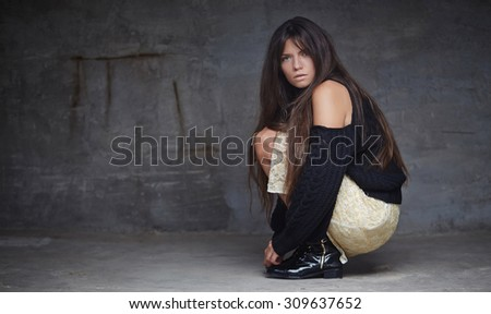 Full body portrait of brunette fashion woman who sitting on the floor over grey wall. #309637652