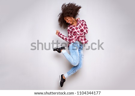 Full body portrait of cheerful young african woman jumping in air over white background #1104344177