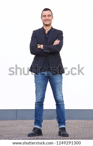 Full body portrait of confident man standing against white wall with blazer and jeans