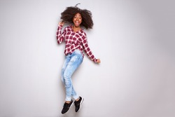 Full body portrait of excited young black woman jumping with joy over white background