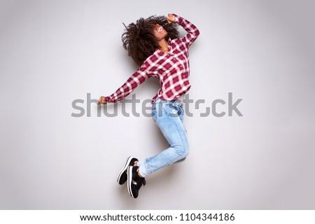 Full body portrait of excited young woman jumping in air against white background #1104344186