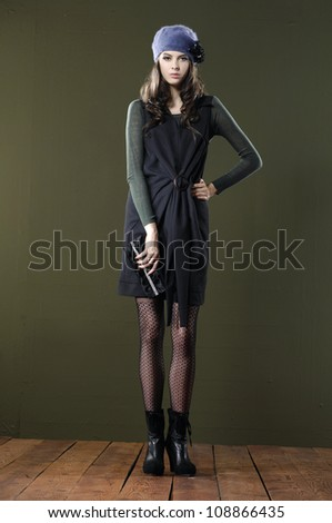 full body Portrait of fashionable woman with purse on floor background