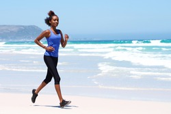 Full body portrait of healthy young female running on the beach