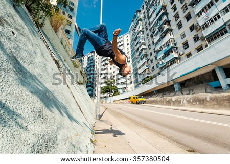 Full body portrait of parkour man jumping high in the street.