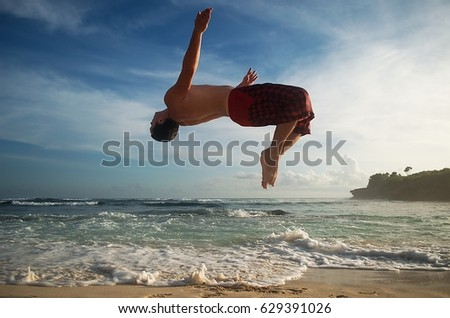 e0d8e88b4 Full body portrait of parkour man jumping high on the beach performing a  back flip