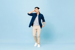 Full body portrait of smiling young handsome Asian man listening to music with wireless headphones isolated on light blue studio background