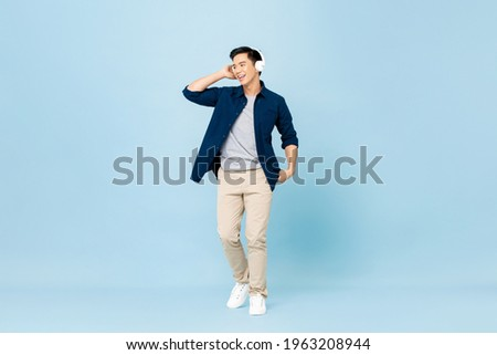 Full body portrait of smiling young handsome Asian man listening to music with wireless headphones isolated on light blue studio background Stock foto ©