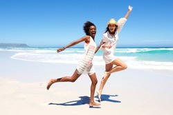 Full body portrait of two young women friends laughing and running on the beach