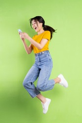 Full body portrait of young asian girl on green background