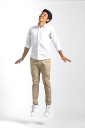 Full body portrait of young Asian man in white casual shirt pose like standing in the air with impress  happiness and sweetly close eyes. Studio shot on white background.