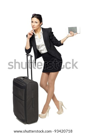 Full-body portrait of young business woman standing with black travel bag and holding the tickets with passport isolated on white background