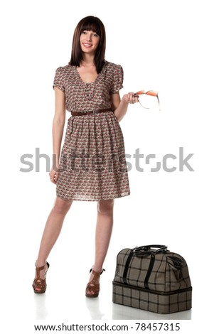 Full-body portrait of young female in dress standing near her travel bag isolated on white background