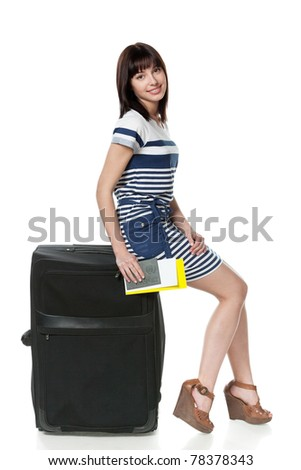 Full-body portrait of young female sitting on her black travel bag and holding the tickets with passport isolated on white background