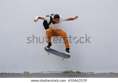 Full body portrait of young male skateboarder doing a trick outdoors