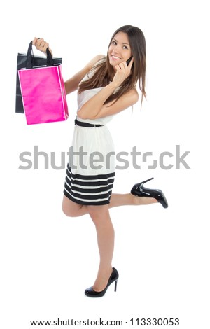 Full body pretty woman shopping bags after successful shopping, smiling and calling on the  mobile phone on a white background