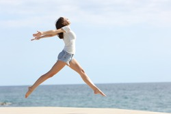 Full body profile of a happy woman with long waxed legs jumping on the beach