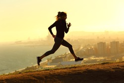 Full body profile of runner woman running at sunset in city outskirts