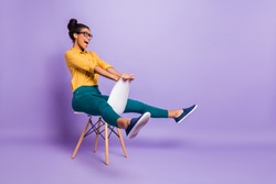 Full body profile photo of amazing dark skin lady sitting on chair between legs like driving car wear specs yellow shirt trousers isolated purple color background