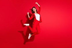 Full body profile photo of attractive lady worker having fun jumping high up good mood celebrate startup success wear blazer suit pants footwear isolated red color background