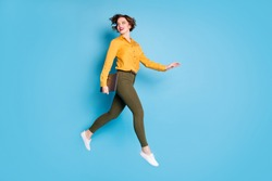 Full body profile photo of beautiful business lady jumping high up hold notebook going conference wear yellow shirt green pants shoes isolated bright blue color background