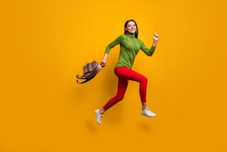 Full body profile photo of funky pretty lady jumping high holding cool youngster bag rushing home after studying wear casual green jumper red pants isolated yellow color background