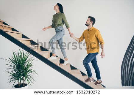 Full body profile photo of handsome guy and his pretty lady leading macho to bedroom going up stairs in modern interior hotel room indoors wear casual clothes Foto stock ©