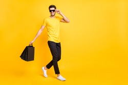 Full body profile photo of handsome guy carry boutique bags abroad shopping go fashionable mall wear casual t-shirt black pants isolated yellow color background