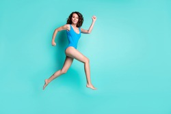 Full body profile photo of motivated adorable young girl lady run jump empty space nice muscles save people beach summer activities advert blue swimwear isolated teal color background