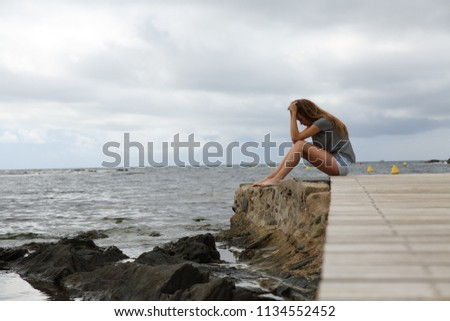 Full body profile portrait of a depressed girl complaining sitting on the beach