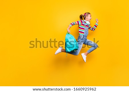 Full body profile side photo crazy schoolchild jump run school discounts hold blue bag rucksack wear striped sweater denim jeans suspenders overalls isolated bright shine yellow color background