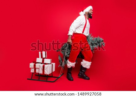 Full body profile side photo of crazy bearded santa claus  scream wow omg pull sledge with prsent wear white stylish hat sweater pants isolated over red background