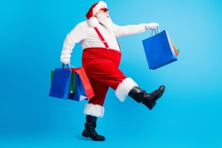 Full body profile side photo of crazy white grey hair bearded fat santa claus go shopping hold x-mas christmas bags wear red suspenders overalls isolated over blue color background