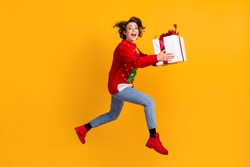 Full body profile side photo of excited girl jump run with x-mas eve noel big gift box, wear christmas tree ornament pullover sweater denim jeans isolated bright shine color background