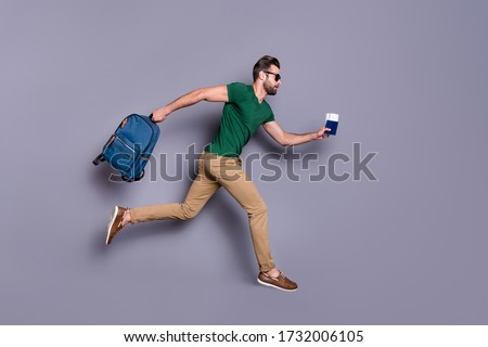 Full body profile side photo of serious guy jump run dont want miss check in passing board hold visa tickets bag backpack wear green trousers isolated over gray color background Foto stock ©