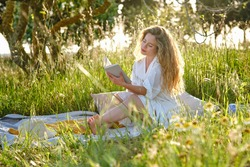 Full body sensitive young female wearing white sundress reading interesting book while resting on blooming abundant lawn in sunny summer countryside