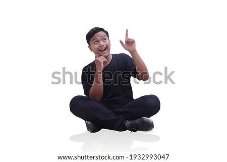 Full body shot of happy Asian man in black clothes sitting isolated against white background. Attractive teenager pointing with his hand to the empty space while the other hand is holding his cheek. Photo stock ©