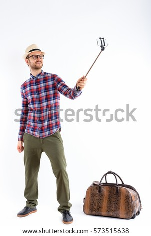 Full body shot of happy young man smiling while holding selfie stick and taking selfie picture with mobile phone ready for vacation