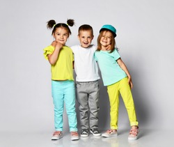 full body shot of three children in bright clothes, two girls and one boy. Triplets, brother and sisters. laughing and screaming loud have fun in the studio
