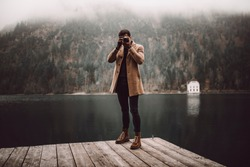 Full body shot of young male photographer in brown coat taking pictures with a small mirrorless camera standing on a lake house deck in lake plansee, Austria