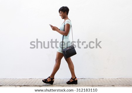 Full body side portrait of a smiling african american young woman walking and looking at cell phone