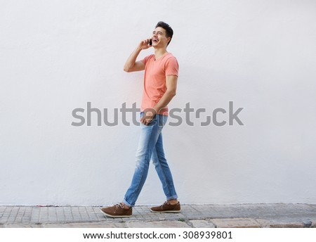 Full body side portrait of a smiling young man walking on sidewalk and listening to mobile phone