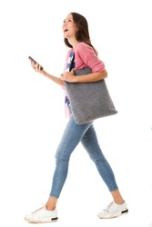 Full body side portrait of fashionable young asian woman walking with purse and smart phone against isolated white background